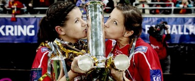 Two female athletes kissing a phallic trophy
