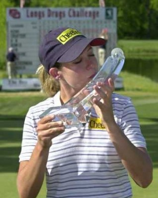 Female golfer kissing a phallic trophy