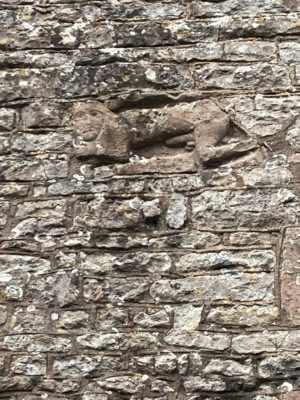 A naked man statue carved in to a stone wall